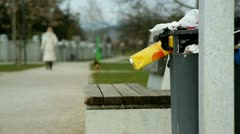 Trash hanging from bin in park Stock Footage