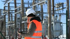 Electrician with computer near the electricity substation - stock footage