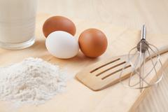 flour, glass of milk, whisk and eggs on wooden table - stock photo