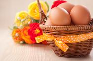 Stock Photo of many eggs in  little basket with yellow bow on wooden table with flowers