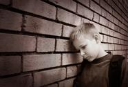 Stock Photo of boy leaning against a wall