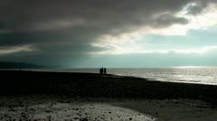 People on Beach, Moody Sky Stock Footage
