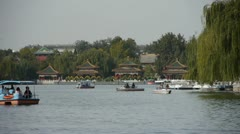 People boating on lake at China Beijing Beihai Park relying on willow island. Stock Footage