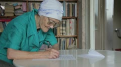 Old woman in glasses writing letter Stock Footage