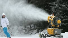 Snow cannon working and skiers passing Stock Footage