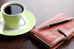 Pen on diary and coffee mug Stock Photos
