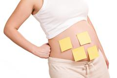 pregnant women with notepaper on her belly - stock photo