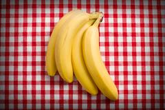 yellow bananas on checkered tablecloth - stock photo