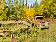 Rusty truck and grader forgotten in fall forest Stock Photos