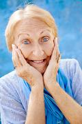 Portrait of surprised senior woman with hands on face on blue background Stock Photos