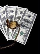 Gold watch on money Stock Photos