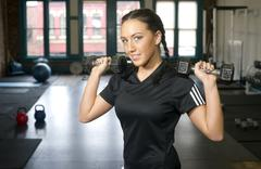 attractive young brunette woman lifts ten pound barbells at gym - stock photo