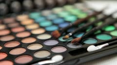 Make-up tools: brushes laying on color cosmetic palette - stock footage