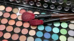 Brushes for make-up applaying on the colorful palette - stock footage