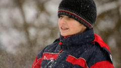 Boy throws snow sideways in winter, close-up - stock footage