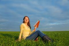 Teen girl reading the bible outdoors Stock Photos