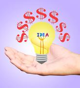 Hand holding an incandescent light bulb isolated on white background Stock Photos