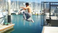 Parkour Athlete Jumps Across the Dock Stock Footage