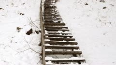 Wooden stairs railings huge steep hill cover snow winter park Stock Footage
