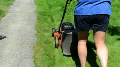 Gardener shorts flip-flop shoes mower cut grass stone path Stock Footage