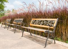 wrought iron bench sitting in the park - stock photo