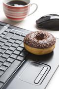 Stock Photo of break in the  office . doughnut on laptop keyboard