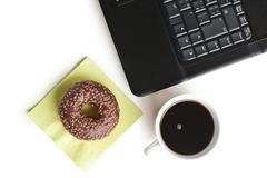 break in the  office . doughnut on laptop keyboard - stock photo