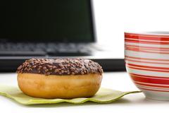 Break in the  office . doughnut on laptop keyboard Stock Photos