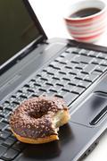 break in the  office . doughnut on laptop keyboard - stock photo