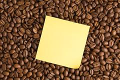 Stock Photo of yellow note paper on coffee beans background