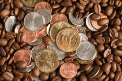 Coins on coffee beans background Stock Photos