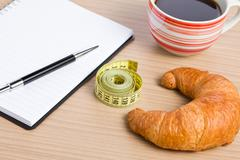 diet concept . croissant and measuring tape - stock photo