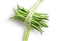 bean pods with measuring tape - stock photo