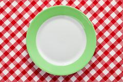 green plate on checkered tablecloth - stock photo