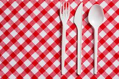Stock Photo of plastic cutlery on checkered tablecloth