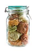colorful pasta tagliatelle in glass jar - stock photo
