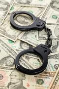 handcuffs on dollars - stock photo