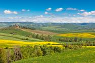 Stock Photo of tuscan farmhouse with green and yellow fields
