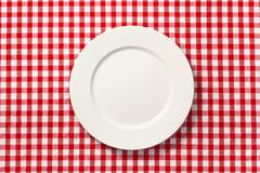 Stock Photo of white plate on checkered tablecloth