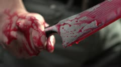 Close up of man gripping bloody knife with blood dripping - stock footage