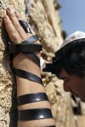 phylacteries wrapped hand on the western wall - stock photo