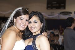 Hispanic bride hugging friend Stock Photos