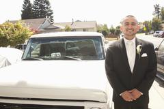 Hispanic groom standing next to truck - stock photo