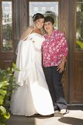 Hispanic bride standing with mother - stock photo