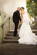 Hispanic bride and groom walking up steps Stock Photos