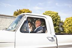 Hispanic bride and father riding in truck - stock photo
