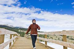 Japanese woman walking across wooden bridge - stock photo