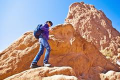 Japanese woman hiking on rocks - stock photo
