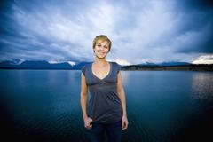 Caucasian woman standing near lake Stock Photos