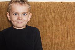 Smiling Caucasian boy sitting on sofa - stock photo